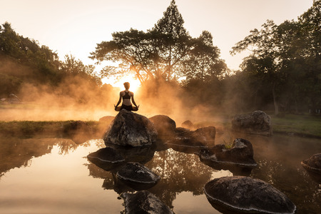 Young girl doing yoga fitness exercise outdoor in beautiful landscape. Morning sunrise Stock Photo