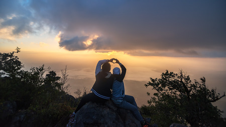 Silhouette of couple makes heart symbol with hand at dusk