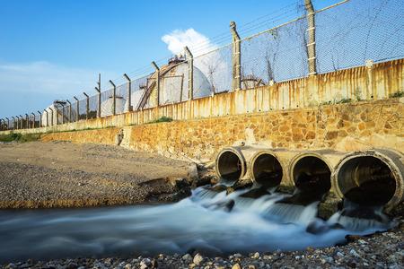 El agua que fluye de una tubería de drenaje hacia el mar, drena en las aguas residuales que fluyen, la costa de las comunidades en Tailandia. Foto de archivo - 92031355