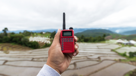 Radio communication(walkie-talkie radio) in hand, on Natural background,Portable radio transceiver in hand, nature on background
