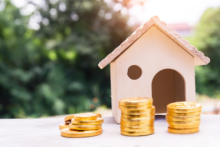 Close up stacking gold coins and home model, the saving with growing your money to real estate owner in the future concept.
