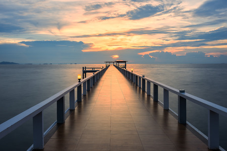 Wooded bridge in the port along sunrise.Wooden pier between sunset in Phuket, Thailand. Summer, Travel, Vacation and Holiday concept.