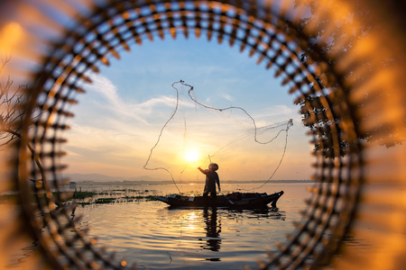 Silhouette of asian fisherman on wooden boat ,fisherman in action throwing a net for catching freshwater fish in nature river Stok Fotoğraf