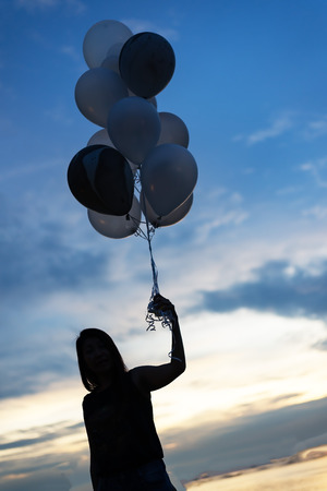 inspiration, joy and happiness concept, silhouette of woman with many flying balloons on the beach , balloons on the background of sunset sky Stock Photo