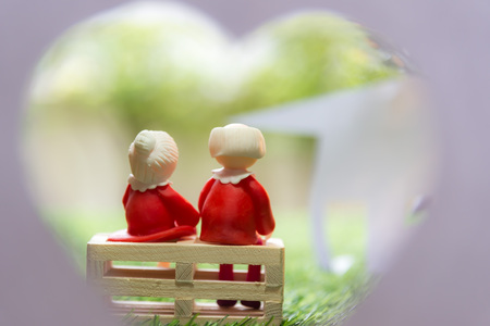 Doll senior couple sitting on wooden chair and looking paper house on the green grass.