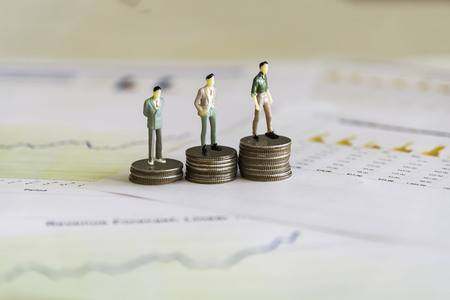 Miniature people: small figures businessmen stand on top of coins. Money, Financial, Business Growth concept.