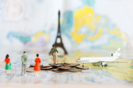 Miniature people with traveling concepts. Group of backpackers walking on passport with stamps. Concept of traveling or exploring the world budget travel Foto de archivo