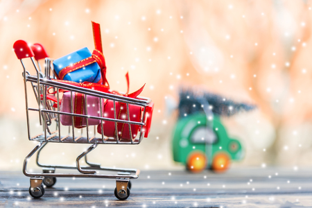 Shopping cart with christmas tree and presents on wooden table
