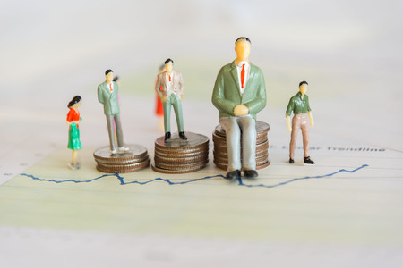 Miniature group businessman standing on money coin stack growing finance graph with project for presenting investment. Investment and Business Concept. 写真素材