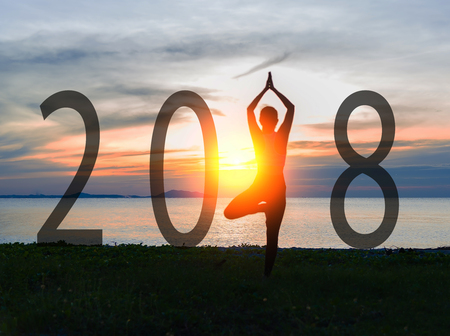 Yoga Happy new year card 2018. Silhouette woman practicing yoga standing as part of Number 2018 near the beach at sunset. Healthy & Holiday Concept.