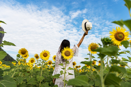 Lady is traveling into Sunflower field.Beautiful girl in field of sunflowers, so happy and relax, select focus