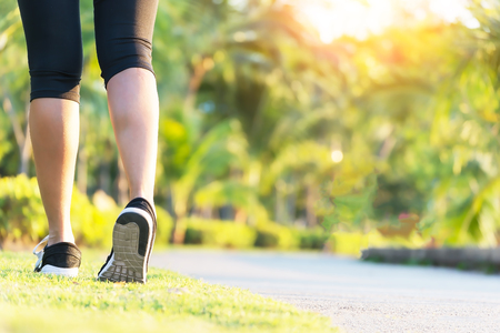 Close up shoes, legs. sport runner woman back view running, girl walking in park. Sport exercise benefit. workout outdoor. weight loss body strong. Slow walking benefits from sport challenge concept. 스톡 콘텐츠