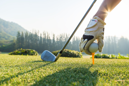 Hand hold golf ball with tee on course, tee off Stock Photo