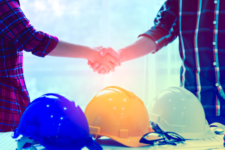 Side view of white helmet and yellow helmet,Team of professional engineers are shaking hands while working in the office center . construction concept .