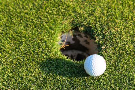 Golf ball on green over a blurred hole. Shallow depth of field. Focus on the ball. Sport Concept ,Lifestyle Concept