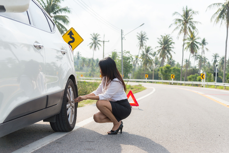 businesswoman in the city with flat tire frustrated repairing a car, unscrew the wheel