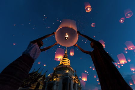Asia woman people release floating lanterns ballon to blue sky