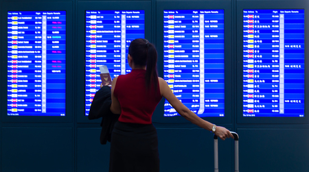 business woman in international airport looking at the flight information board, holding passport in her hand, checking her flight:business