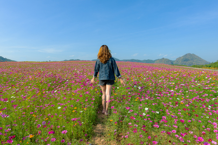 Tourist asian woman relax and freedom in beautiful blooming cosmos flower garden. Travel and Lifestyle Concept.