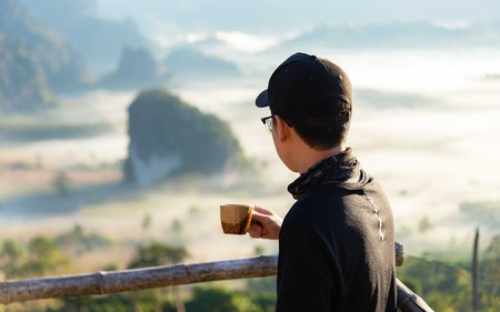 Relax winter style.Asia man wearing a black shirt holding a cup of coffee with smoke backdrop mountain nature. during mist sunrise , relax and freedom day. Lifestyle Concept. Banco de Imagens