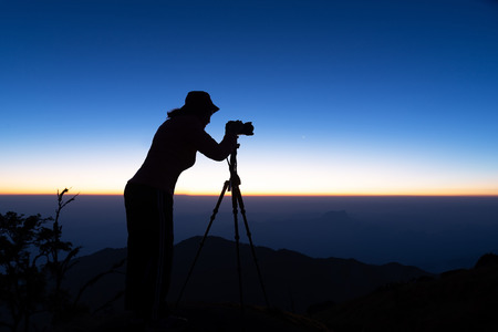 Silhouette of woman shooting with camera at sunset . Travel Concept