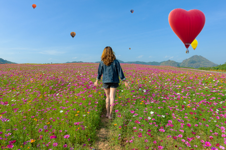 Little girl Happy and Balloon summer Sunny day and blue sky, happy Beautiful cosmos flowers, Thailand.