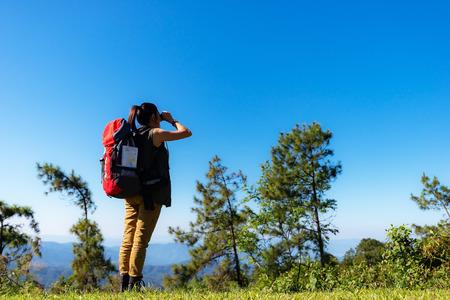Hiker woman look binoculars on the mountain, background blue sky Banco de Imagens