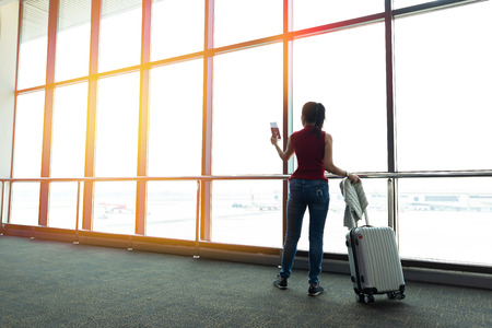 Young woman is standing near window at the airport and watching plane before departure. She is standing and carrying luggage.Travel Concept Banco de Imagens