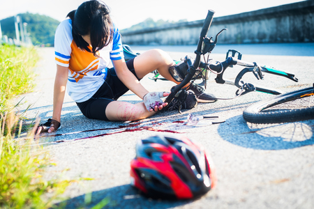 accident clashed on young woman bicyclist in hurt and injured at knee of leg, after accident clashed, with mortal wound and bleeding of blood flow on the surface of street road