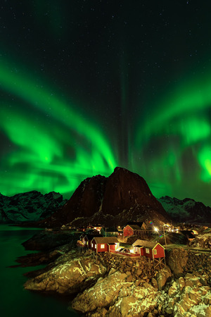 Northern lights over the mountains and fishing huts in the village , Norway Фото со стока