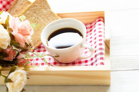 Fresh morning coffee with bread, rose in tray on the bed, early work day. Lifestyle Concept Фото со стока