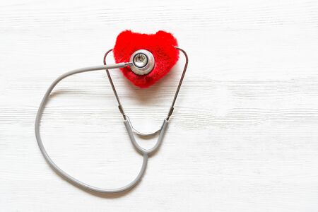 Close up hand holding stethoscope to check red heart on white isolated background, health medical technology concepts
