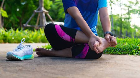 Young woman holding ankle in pain on the stadium track. Broken twisted joint running sport injury. Athletic woman touching foot due to sprain. Healthy Concept