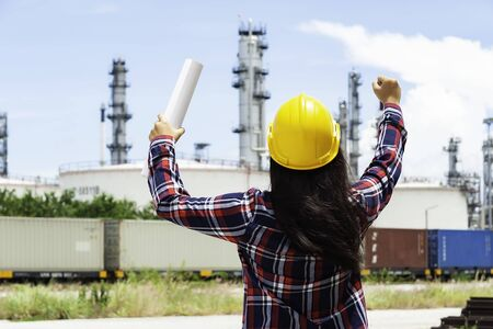 Young women engineer builder looking thoughtfully at refinery construction project, Engineer Concept,professional,safety,industry 写真素材