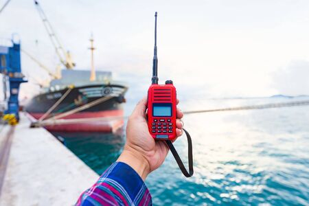 Engineer and crane , smiling dock worker hand holding walkie talkie and Container ship and ship background Фото со стока
