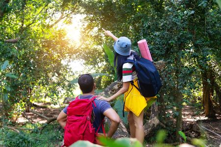 Couple asian traveler with backpack adventure holding map to find directions. People friend walking relax in jungle forest outdoor for destination leisure education nature in vacation. Travel Concept Фото со стока