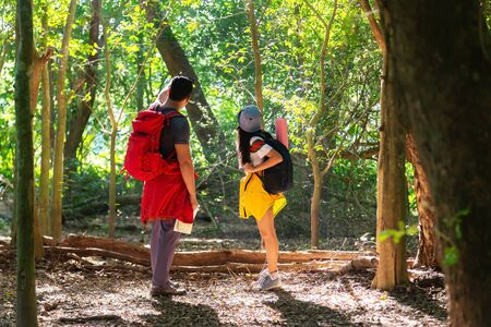 Traveler with backpack adventure holding map to find directions in the jungle forest outdoor for study and education nature. Travel and Lifestyle Concept