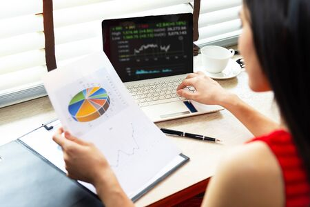 Asian businesswomen holding a pen and analysis documents on office table with laptop computer and graph financial diagram working in the background. Business Concept. Фото со стока