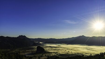 The moving flow of the mist or foggy in between the hills of mountains Фото со стока