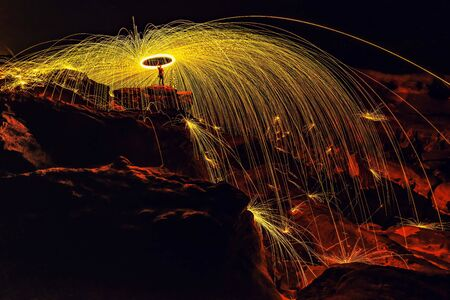 Showers of hot glowing sparks from spinning steel wool on the rock and beach