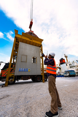 foreman stevedore working in yard terminal of the port checking safety equipments readiness for start loading cargo anytime, lifting by gantry crane, working at risk on the high level insurance Редакционное