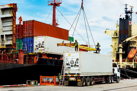 container ship in import export and business logistic.By crane , Trade Port , Shipping.Tugboat assisting cargo to harbor and discharging shipment being for transports sea to international worldwide Редакционное
