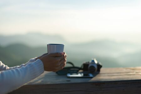 Portrait of the beautiful woman holding a cup of coffee in the morning,mountain view behind, relax and freedom day. Lifestyle Concept.