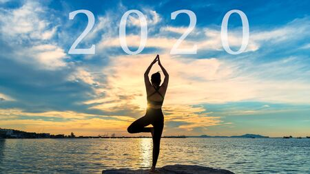 Happy new year card 2020. Silhouette lifestyle woman yoga near the beach at sunset. Healthy and Holiday Concept Фото со стока