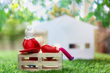 Miniature people, man and woman with mini house on green nature bokeh background using as relationship and family concept. Banque d'images