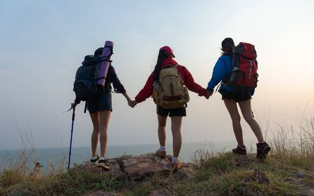 Hikers with backpacks walking through a meadow with lush grass. Two young Asian female hipster hiking on mountain holiday. Background for Travel concept. Camp forest adventure travel relax concept