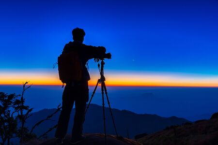 The silhouette of the photographer is shooting the scenery at the top of the mountain while the sun is falling. Travel inspiration concept.