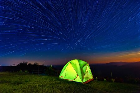 Star circles above the night mountain forest and a glowing camping tent