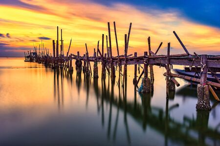 Old wood bridge for small fishing boat at fisherman village with sunset