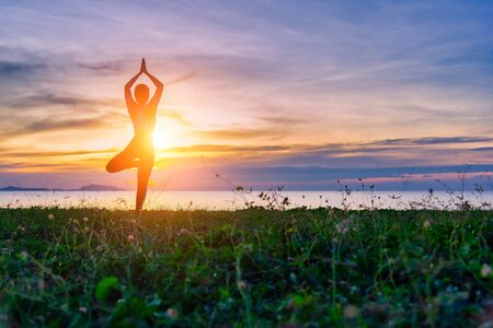Silhouette healthy woman lifestyle exercising vital meditate and practicing yoga . Healthy Concept.